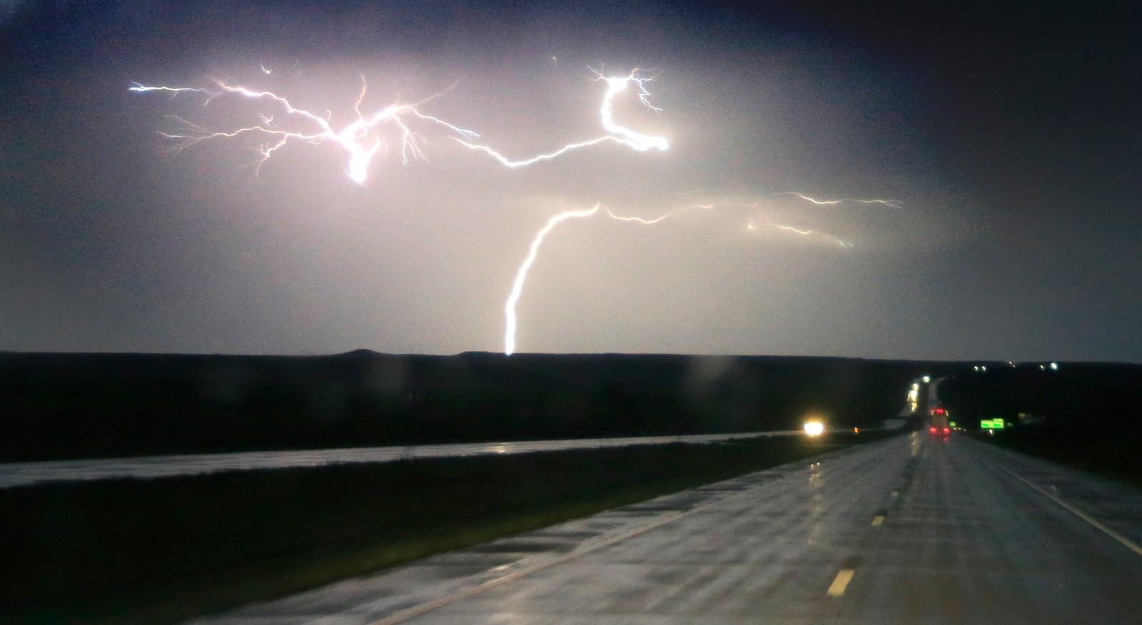 Lyn flerrer himmelen over Interstate 70 ved Junction City i Kansas, USA. Tordenbygene hadde med seg store haglbyger og vind opp mot orkan styrke.