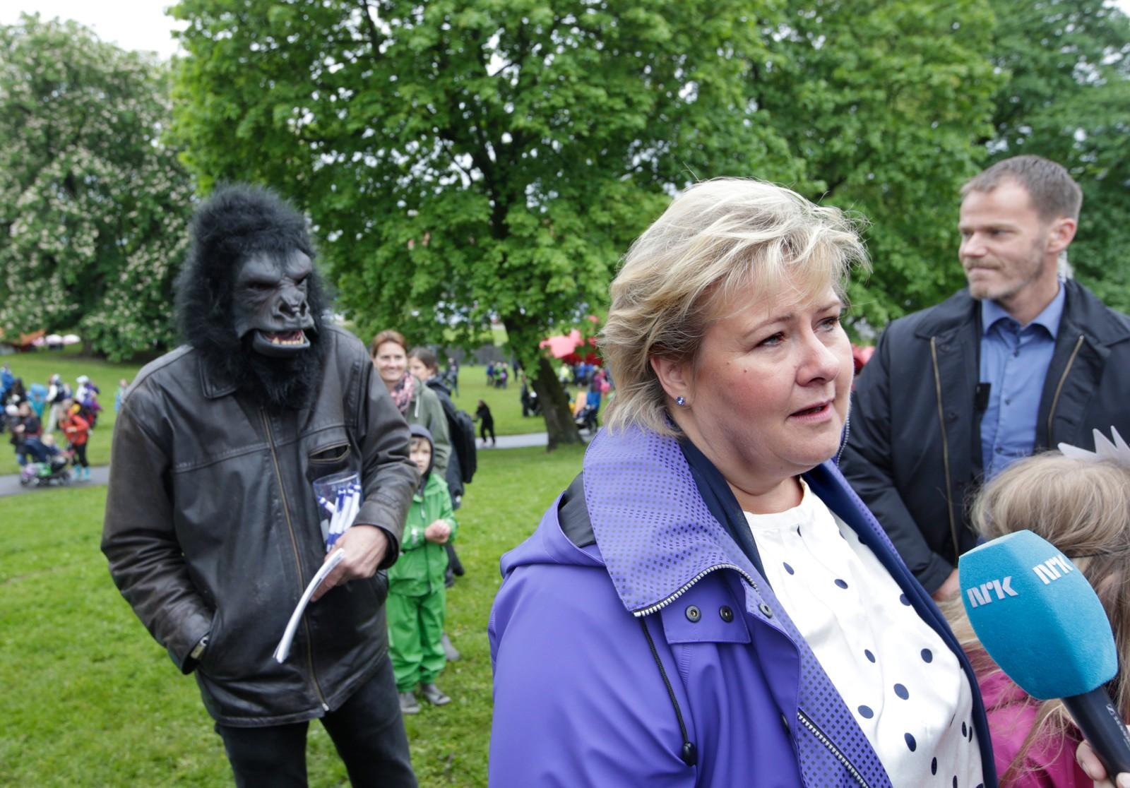 Statsminister Erna Solberg under et besøk på barnefestivalen Miniøya på Tøyen i Oslo 30. mai. Mens statsministeren ble intervjuet av NRK ble hun passet av en gorilla.