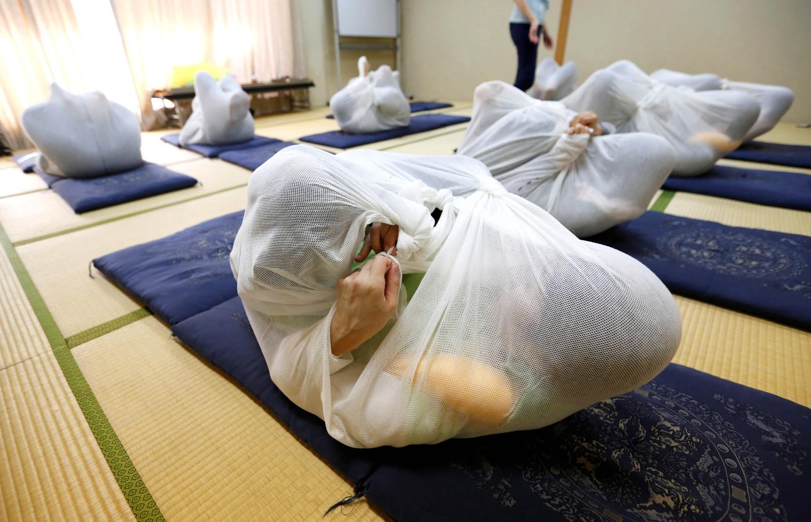"""Dette kalles Otonamaki, som kan oversettes med """"vokseninnpakking"""". Det er en ny form for terapi som skal forbedre holdningen og lindre stivhet i kroppen. Det tror de i alle fall her i Asaka i Japan."""