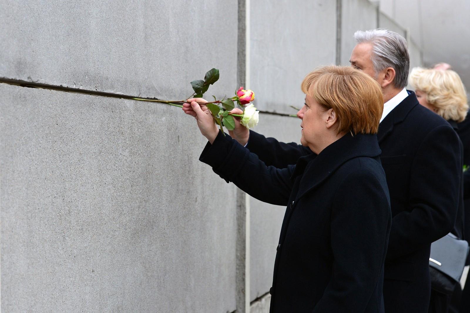 Angela Merkel og Berlins ordfører Klaus Wowereit  fester roser i en rest av muren.