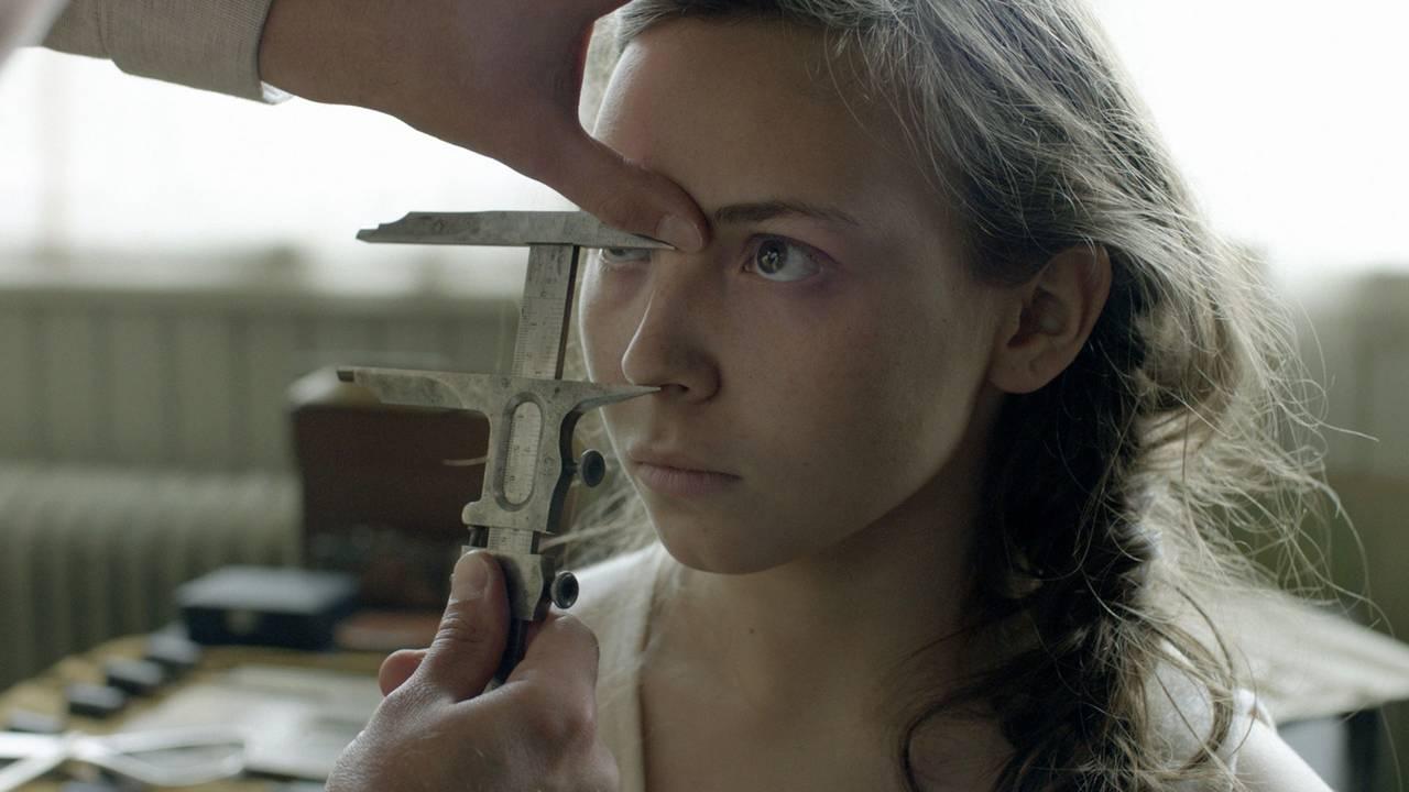 Lene Cecilia Sparrok i filmen Sameblod. Ung jente med fletter blir mål i ansiktet med et instrument.