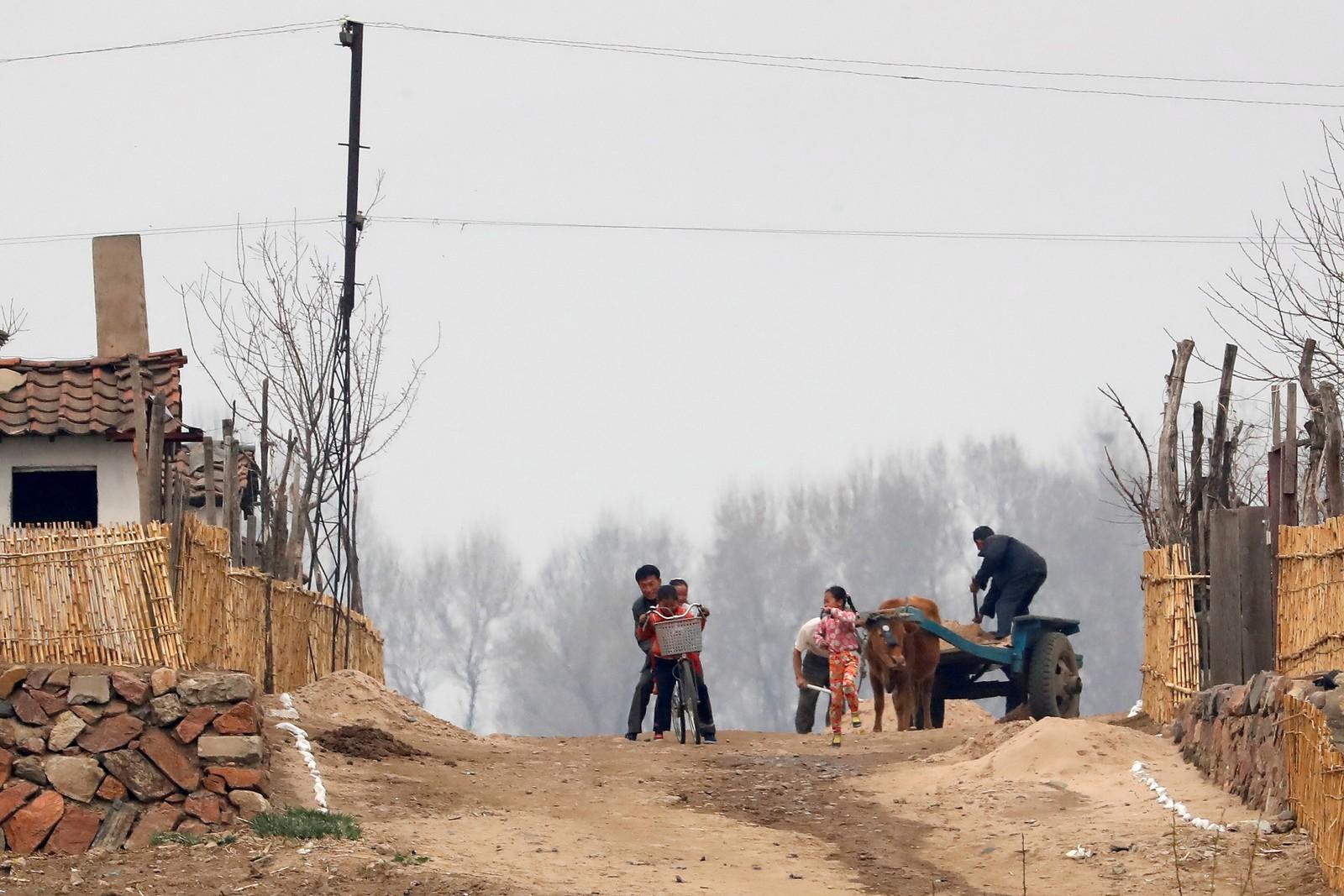 Arbeidere og barn ved elva Yalu ved grensen mot Kina.