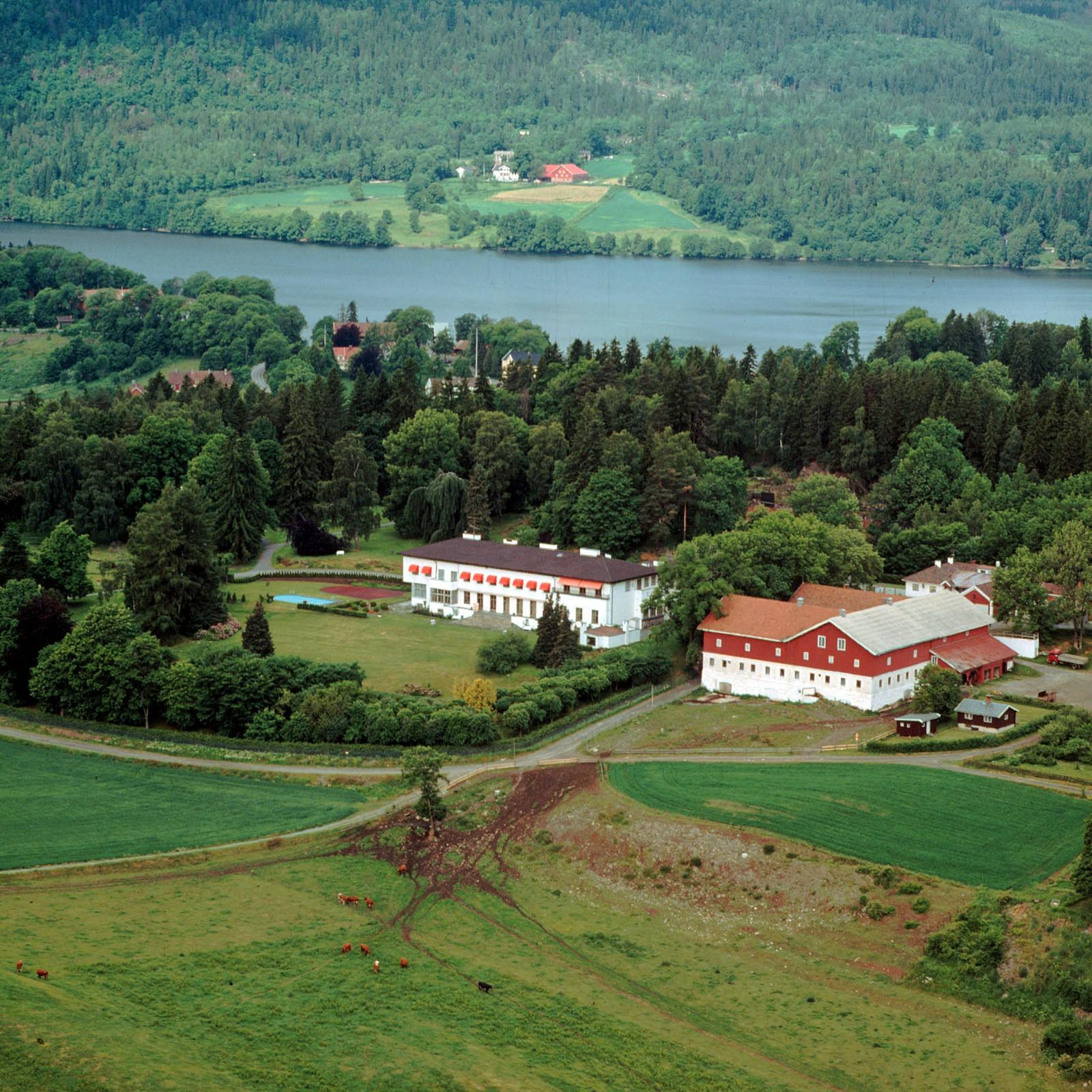 Flyfoto av kronprinsfamiliens bolig, Skaugum gård, i Asker. Semsvannet i bakgrunnen.