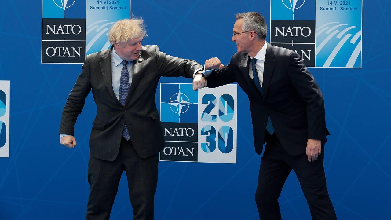 Storbritannias statsminister Boris Johnson tar en koronahilsen på Natos generalsekretær Jens Stoltenberg før toppmøtet.
