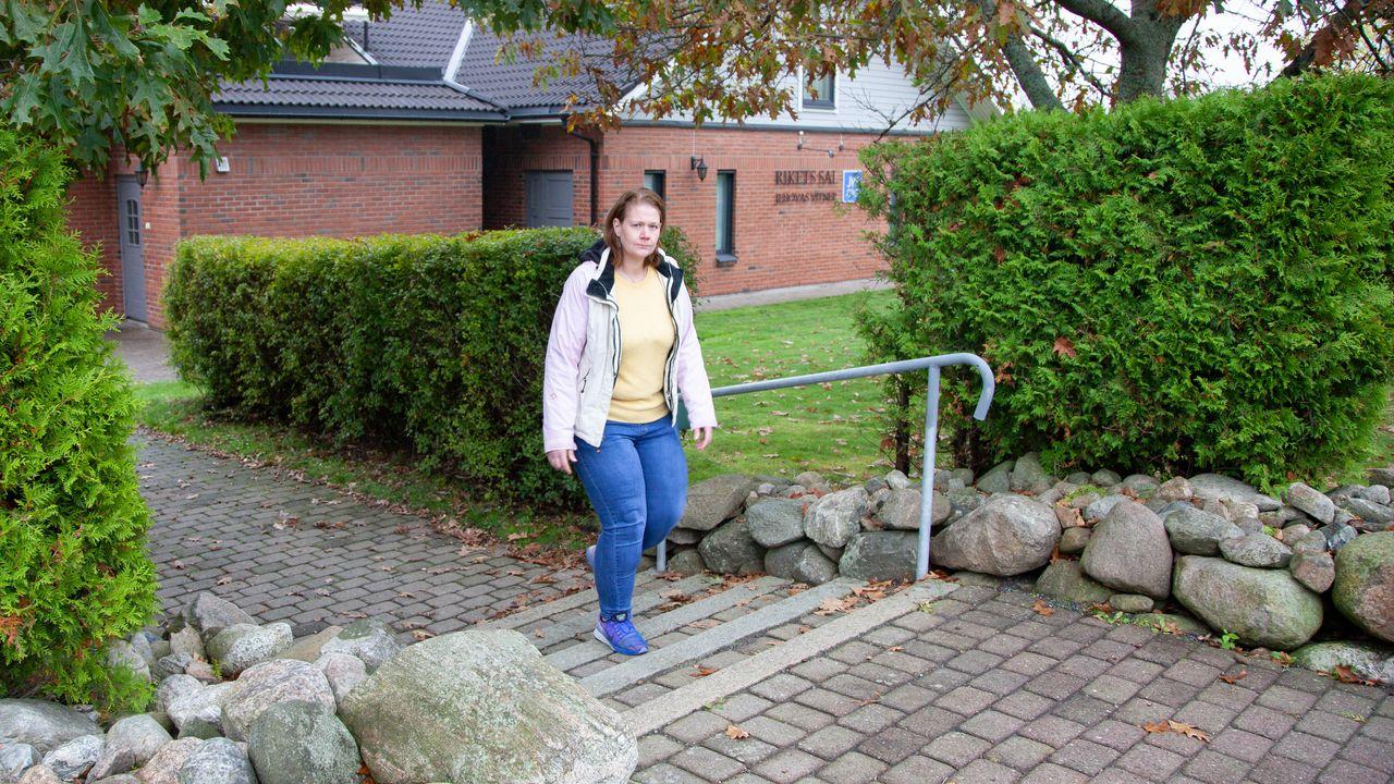 Ramona Solgård går opp en trapp med grønne busker på sidene. Rikets Sal i bakgrunnen.