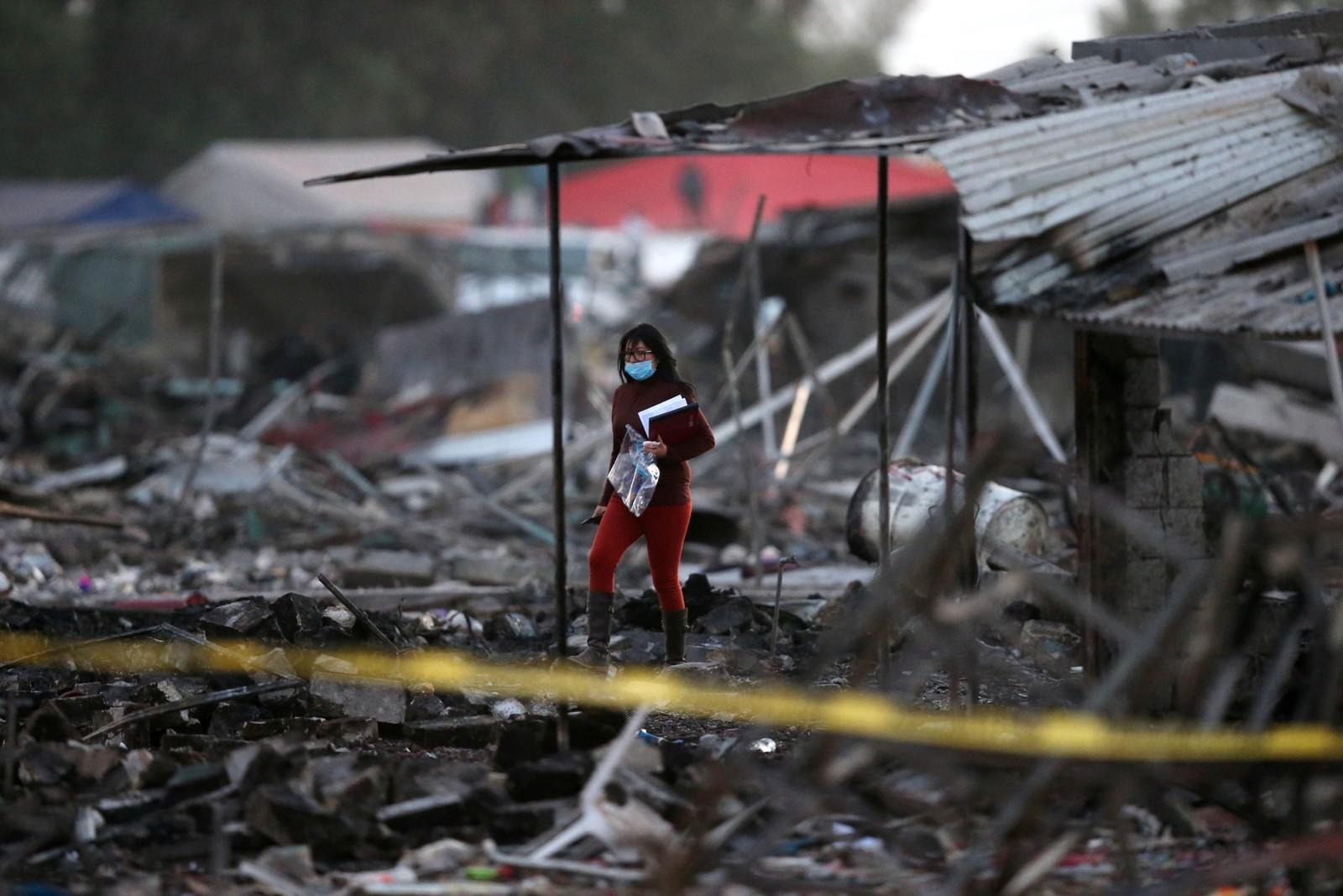En kvinne står i ruinene etter flere eksplosjoner på et fyrverkerimarked i San Pablito i Mexico.