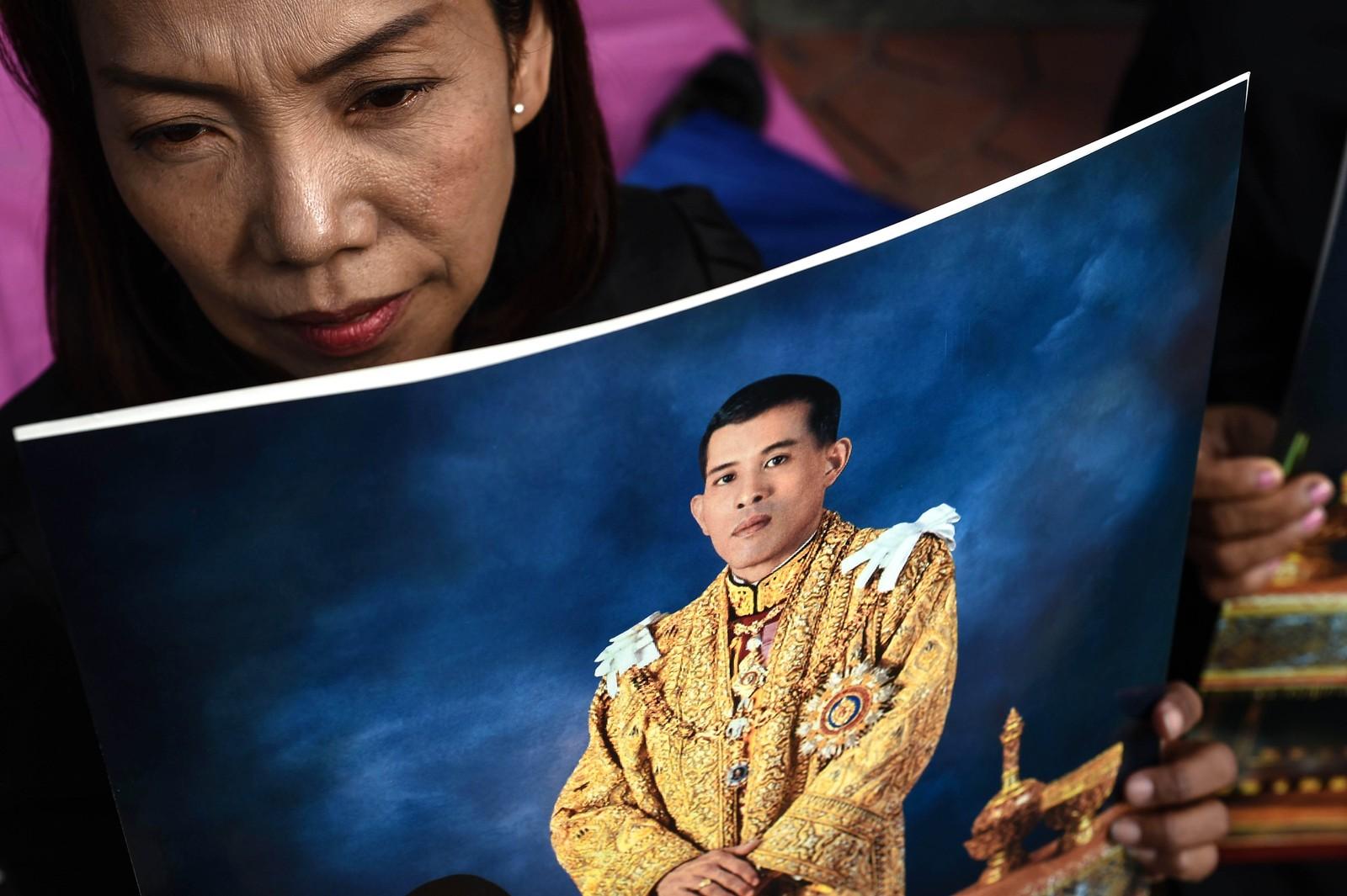 En kvinne holder et bilde av Maha Vajiralongkorn som ble innsatt som konge 1. desember.