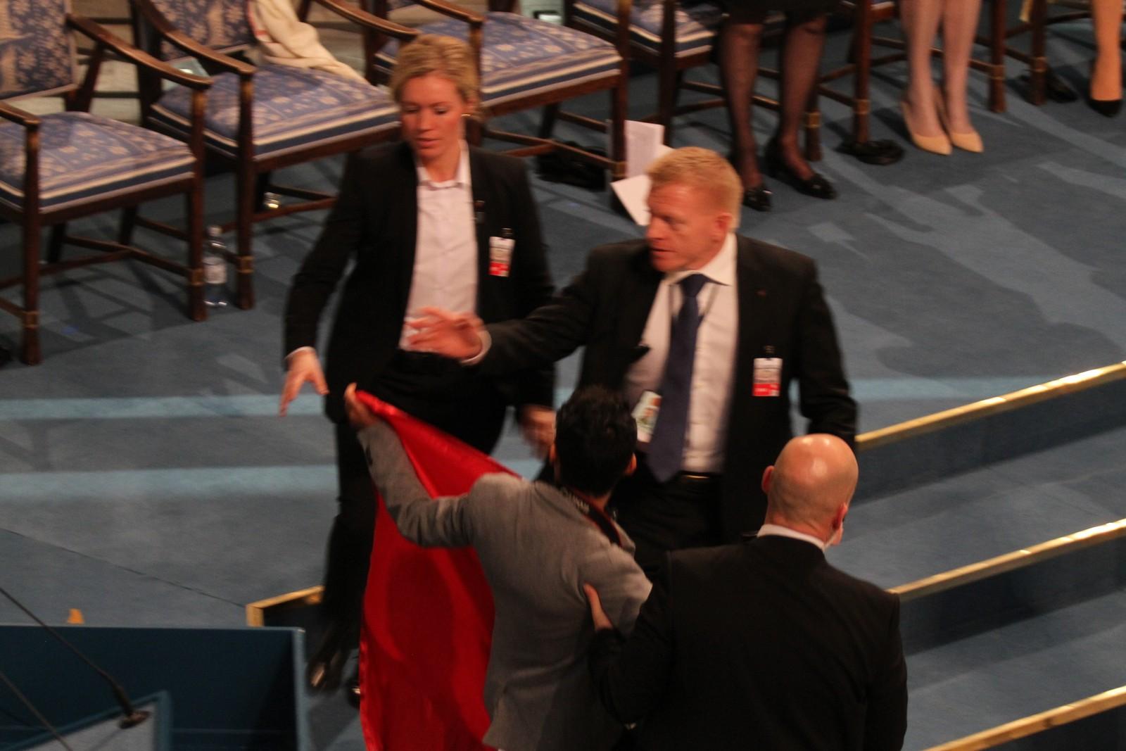 STORMET SCENEN: En ung mann kastes ut etter å ha gått på scenen foran Malala. Han hadde med seg et flagg.
