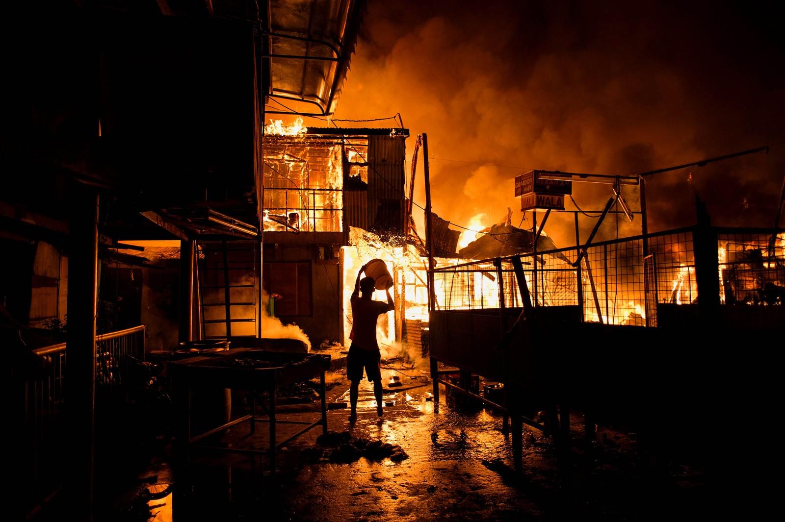 En mann kjemper en desperat kamp mot flammene under en brann i Delpan i Manila. Brannen ødela flere hundre hjem.
