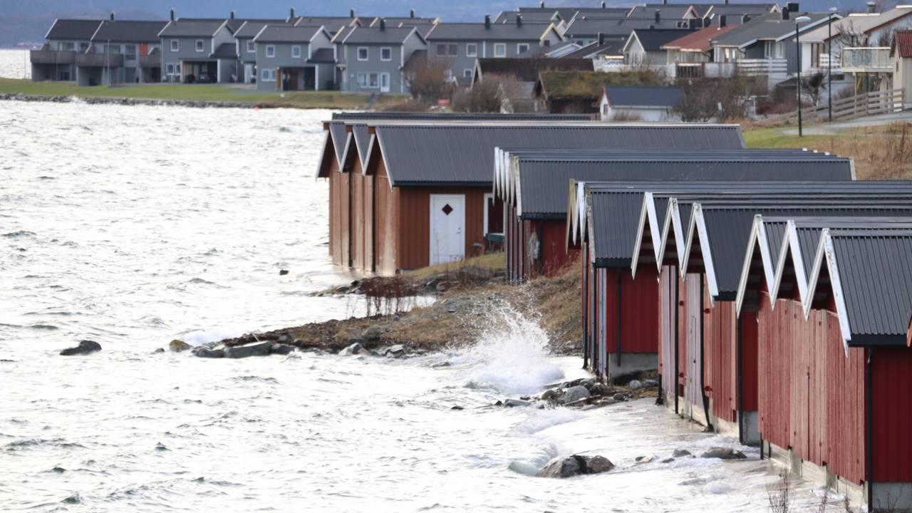Vannet slår mot båthusene i Brekstad i Trøndelag.