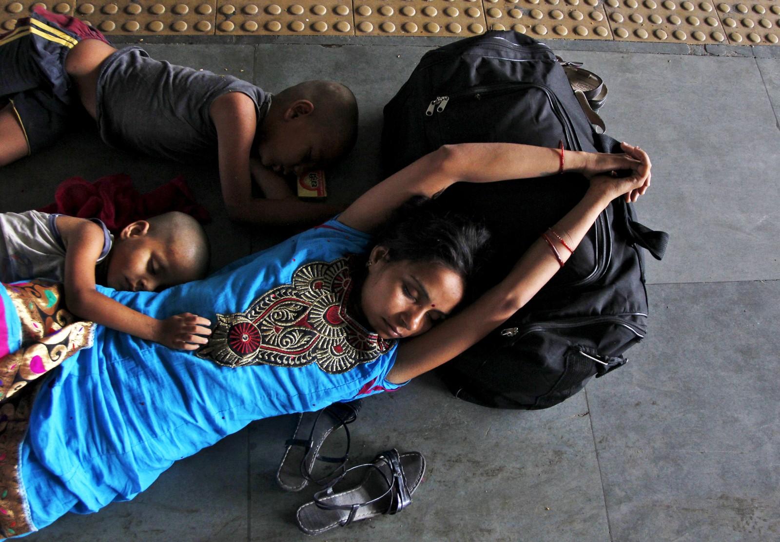 Kivnne og barn sover på perrongen på jernbanestasjonen i Allahabad i India.